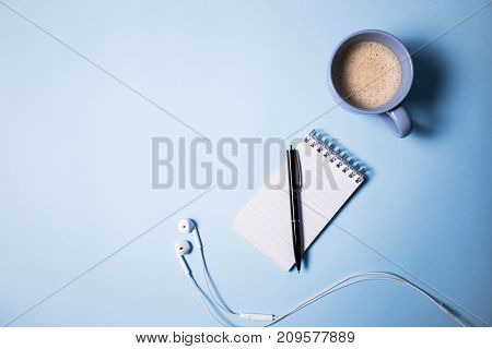 Office supplies. Top view on opened notebook, pen, headphone, laptop and cup of coffee on blue.