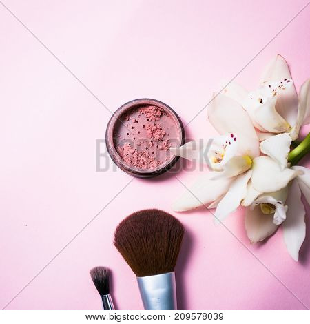 Powder, brush and flower on pink background