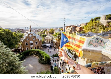 Holding catalan flag on the cityscape background in Guell park in Barcelona