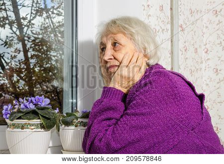 Old lonely woman sitting near the window in his house with flowers