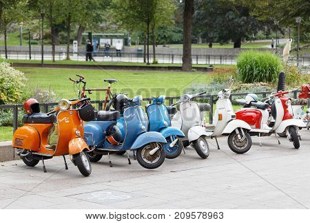 STOCKHOLM SWEDEN - SEPT 02 2017: Many parked retro vespa scooters in the city park at the Mods vs Rockers event at the Saint Eriks bridge Stockholm Sweden September 02 2017