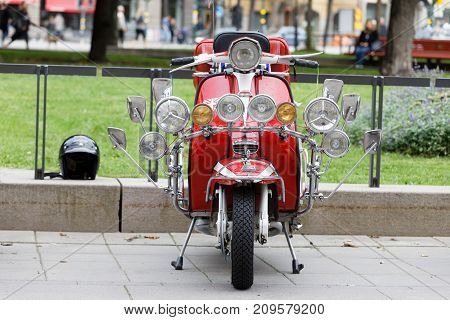 STOCKHOLM SWEDEN - SEPT 02 2017: Lots of lamps on a modified old fashioned classic vespa scooter at the Mods vs Rockers event at the Saint Eriks bridge Stockholm Sweden September 02 2017