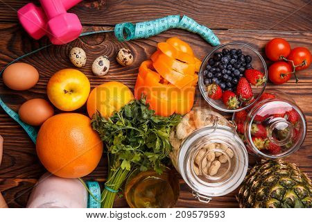 The concept of dietary nutrition with pineapple, orange, grapefruit, apple, sweet pepper and measuring tape, eggs and greens, blueberries, strawberries, tomatoes and rampant eggs