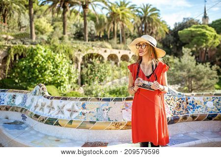 Young woman tourist in red dress visiting famous Guell park in Barcelona