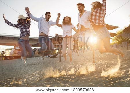 Group of friends together on beach jumping and having fun
