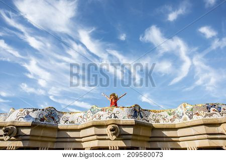 View on the beautiful terrace decorated with mosaic with happy woman tourist in Guell park in Barcelona. Wide angle view with copy space