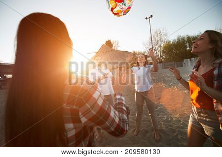 Group of young cheerful friends playing with ball at beach
