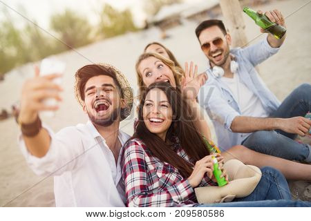 Group of young cheerful friends having great time at beach