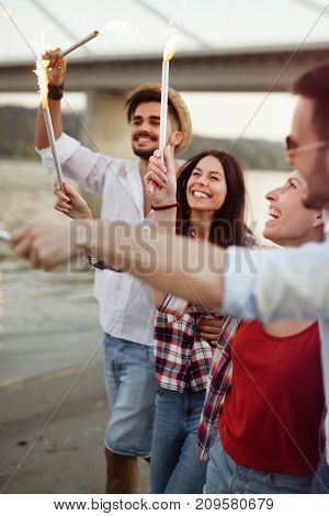 Picture of happy friends holding burning sparkles at beach