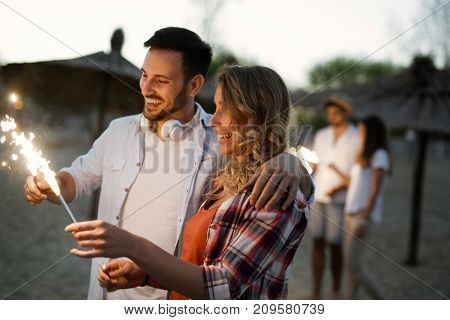 Picture of happy couple holding burning sparkle at beach