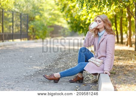 Beautiful blonde in a pink coat sits on a curb in a park with coffee. In full growth. Concept - rest.
