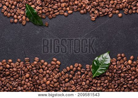Coffe beans with coffe leaves on black slate background.