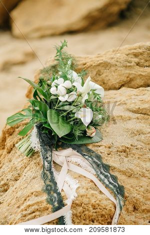 bouquet of a bride from feces and roses lies on a sandstone stone on the seashore