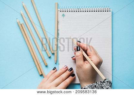A woman with a beautiful manicure draws in a notebook