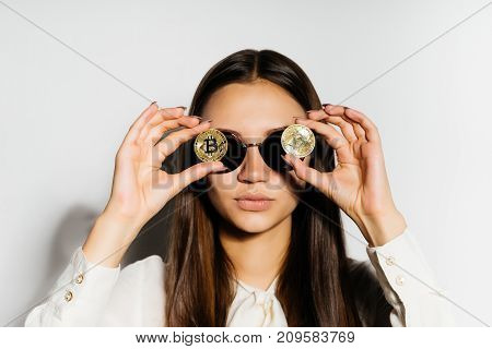 steep, serious girl with black glasses put a coin to her eyes. Money, electronic money, crypto currency, bitcoins, isolated