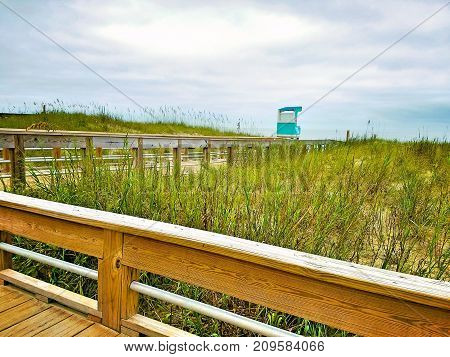 A beach boardwalk view with a lifeguard tower in the background.