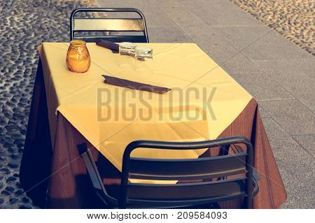 Toned image of table with yellow tablecloth and chairs on street cafe