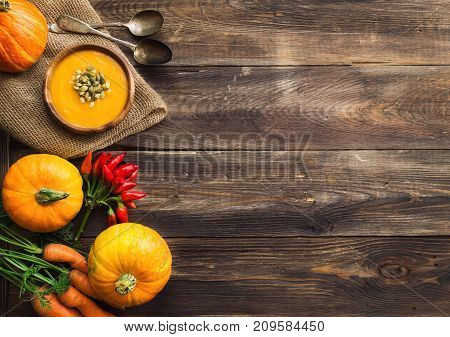 Fresh homemade pumpkin soup with ingredients on wooden rustic background. Top view. Copy space area.