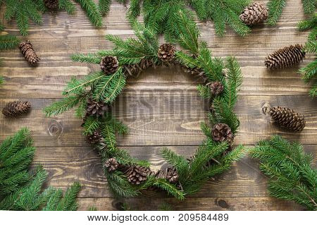 Christmas Wreath With Fir Branches And Pine Cone On Wooden Tabletop. Flat Lay.