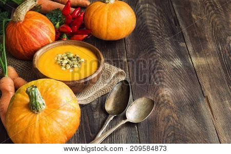 Fresh homemade pumpkin soup with ingredients on wooden rustic background. Copy space area.
