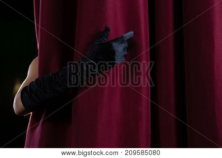 Close-up of hand in a black glove pulling curtain away