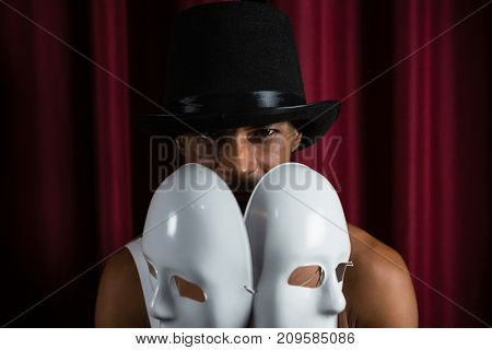 Artist holding two white mask in stage
