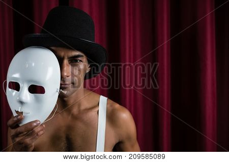 Artist holding white mask in stage