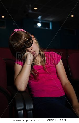 Girl wearing 3d glasses while sleeping in theater