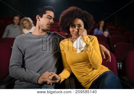 Sad couple watching movie in theatre