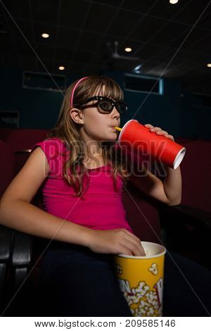 Girl wearing 3D glasses while having drink and popcorns during movie in theater