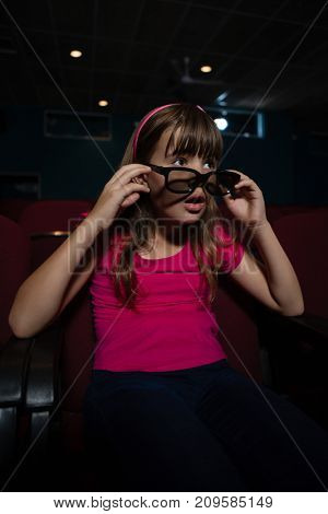 Girl using 3D glasses while watching movie in theater