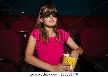 Girl using 3D glasses while having popcorns during movie in theater