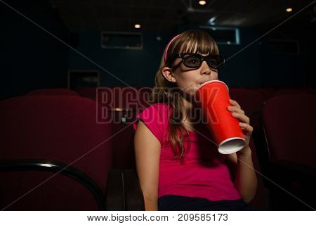 Girl wearing 3D glasses while having drink during movie in theater