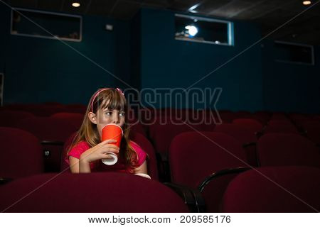 Girl having drink while sitting on seat in movie theater