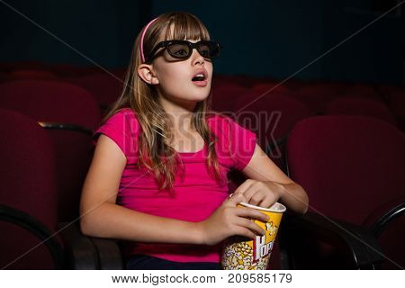 Surprised girl using 3D glasses while having popcorns during movie intheater