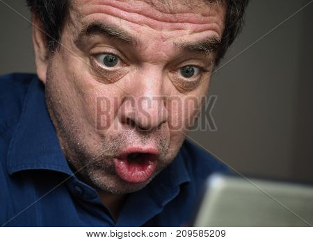 Bad news. Close-up portrait of a surprised man with a smartphone