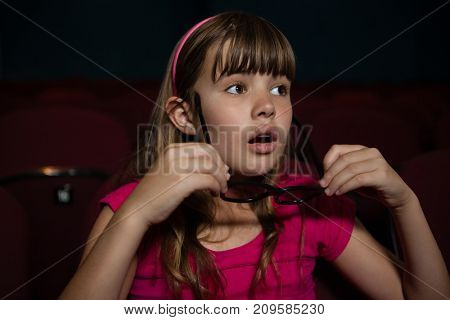 Girl wearing 3D glasses while watching movie in theater