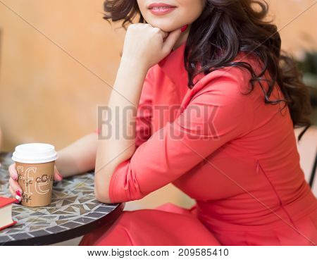 A woman with dark hair in a red dress is holding a cardboard glass with coffee sitting at a table in a cozy cafe. A woman enjoys a good coffee and expects a friend in a cafe