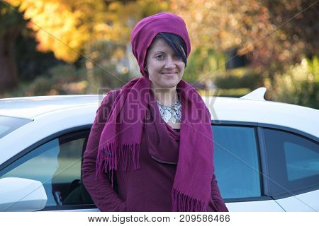 Woman leaning on car in fall/autumn seasonal style fashion