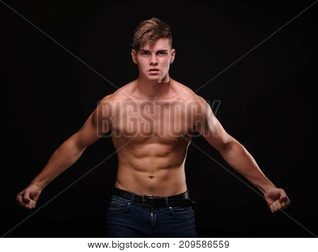 Portrait of a passionate, strong, masculine young man with a perfect torso and muscular arms, posing shirtless on a black background. poster