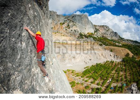 A Rock Climber In A Hat On A Rock.