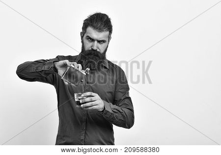 bearded man long beard brutal caucasian hipster with moustache holding metallic flask jar and glass with alcoholic drink whiskey has serious face in orange shirt isolated on white background