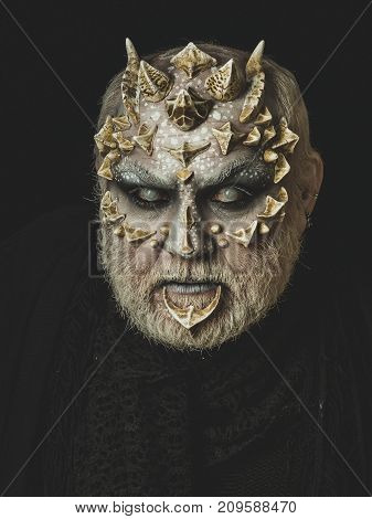 Demon baring teeth on black background. Monster with thorns and horns. Evil face with dragon skin and grey beard. Man angry with blind eyes. Horror and fantasy concept.