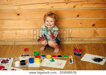 Arts and crafts. Boy painter painting on wooden floor. Kid learning and playing. Child happy smiling with colored hands gouache paints and drawings. Imagination creativity and freedom concept.