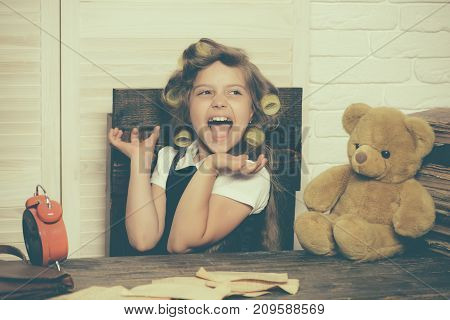 Small girl with curler in hair. Little baby secretary with bear. Kid choose career. Child with alarm clock. Education and childhood.