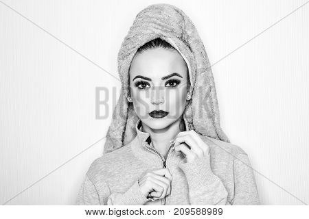Sexy young woman with beautiful makeup on face and pink terry towel on head with red lips isolated on white background
