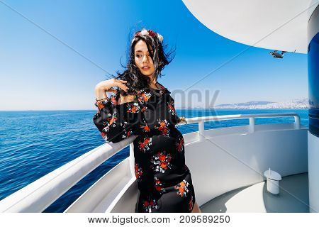 girl with black hair enjoys relaxing on a yacht