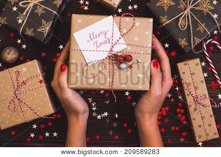 Woman hands holding christmas holiday gift box with postcard merry xmas on decorated festive table with sparkle stars candy cane walnut on wooden background. Packaging gift wrap and ribbons twine. Winter time new year