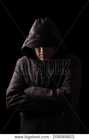 Lonely, depressed and fragile man hiding face, arms crossed and standing in the darkness. Low key, black background. Concept for loneliness, depression, sadness and mental health issues
