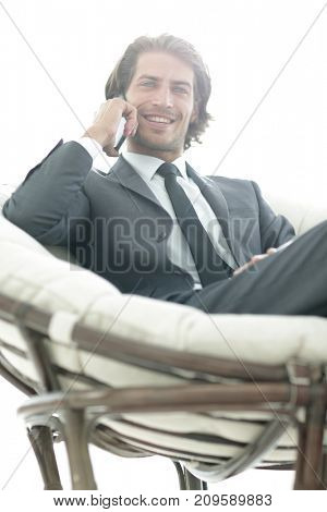 business man talking on a smartphone while sitting in a comfortable chair.